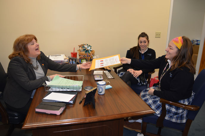 Claire Mulhall, a junior at Mercy Academy, passed information to Rep. Joni Jenkins of Shively at her office in Frankfort, Ky., on Feb. 8 as Mercy junior Lexi Newton looked on. Mercy students spent the day at the capitol, attending committee meetings and speaking with legislators. The students spoke with Rep. Jenkins about abolishing the death penalty and capping interest rates on payday lending. (Photo Special to The Record)