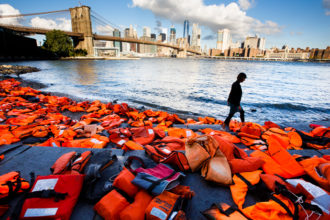 "A woman in New York walks past hundreds of refugee life jackets collected from the beaches of Greece Sept. 16, 2016. The U.S. bishops in a pastoral reflection released March 22 called all Catholics to do what each of them can ""to accompany migrants and refugees who seek a better life in the United States."" (CNS photo/Justin Lane, EPA)"