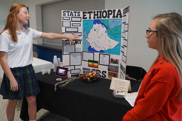 St. Stephen Martyr School eighth-graders Amelia Cassin, left, and Gracie Gilkey presented a project they created about Catholic Relief Service's work in Ethiopia prior to the CRS Rice Bowl Luncheon at Sacred Heart Academy Feb. 23.