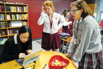 Yufei Wang, left, Maggie Jordan, center, and Sara Bruner, leaders of Assumption High School's Global Outreach Club, worked during a meeting last month. (Photo Special to The Record)