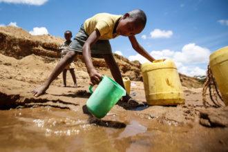 A boy collects water in a dry riverbed in Kitui, Kenya, in this 2015 file photo. (CNS photo/Dai Kurokawa, EPA)