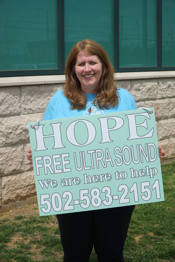 Laura Grijalba, a parishioner of St. Patrick Church, holds a sign with the word hope in large letters and the number to the Little Way Pregnancy Resource Center. (Record Photo by Jessica Able)