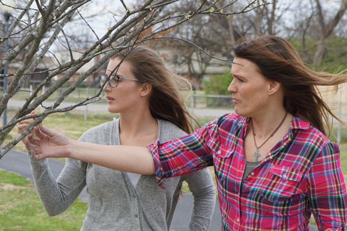 Record Photo by Ruby Thomas Cayley Crum, left, and Colleen Crum, the daughter and mother duo who founded ReTree Shively, stopped March 20 to look at a redbud, one of the trees planted in Shively Park.