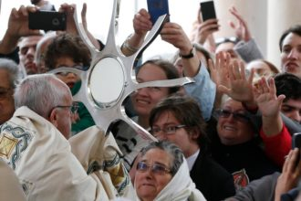 Pope Francis blesses the sick with the Eucharist at the conclusion of the canonization Mass of Sts. Francisco and Jacinta Marto, two of the three Fatima seers, at the Shrine of Our Lady of Fatima in Portugal May 13. The Mass marked the 100th anniversary of the Fatima Marian apparitions, which began on May 13, 1917. (CNS photo/Paul Haring)