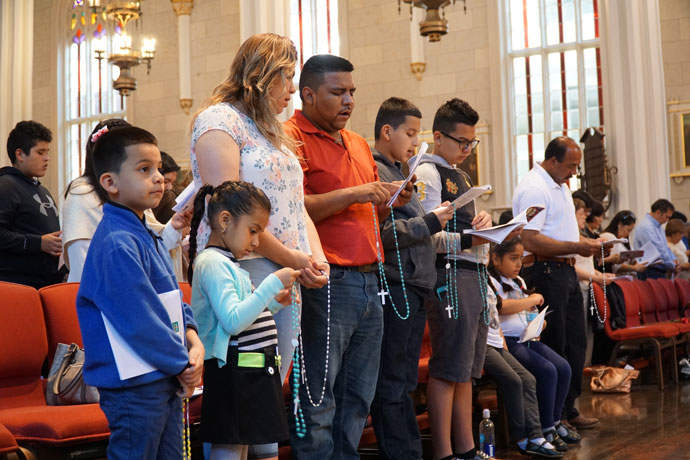 A family, above, prayed the rosary prior to a Mass honoring Our Lady of Fatima May 13 at the Cathedral of the Assumption in downtown Louisville.
