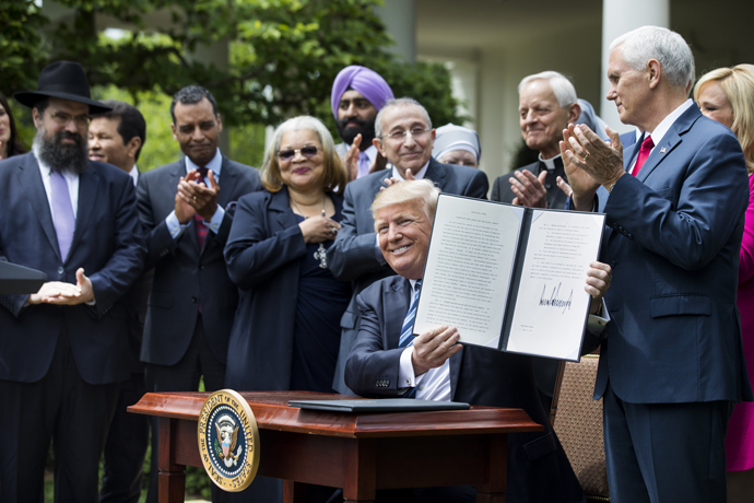 President Donald Trump shows his signed Executive Order on Promoting Free Speech and Religious Liberty during a National Day of Prayer event at the White House in Washington May 4. (CNS photo/Jim Lo Scalzo, EPA)