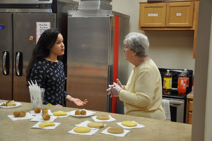 Daisy Baez, left, and Mimi Graves chat in the kitchen of Christ Chapel on April 27. Baez is the chapel's women and children's associate, and Graves, a parishioner of St. Margaret Mary Church, serves as a volunteer.