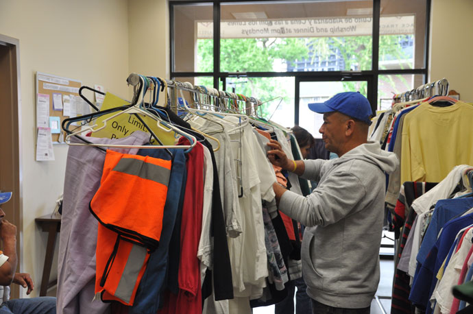 "Rejino Fernandez selects items from Christ Chapel's ""clothing closet"" April 27."