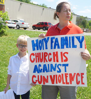 Beth Nett and her nephew Xavier Mudd, members of Holy Family Church, stood at 29th and Broadway May 13 during the Hands Across Louisville event. Record Photo by Ruby Thomas