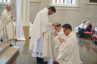 Father Michael Wimsatt, director of the Vocations Office, laid his hands on Father Martin. The laying on of hands is an ancient gesture signifying the conferral of the Holy Spirit.