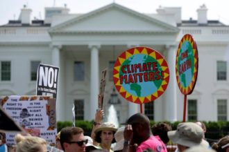 Protesters carry signs during the People's Climate March April 29 outside the White House in Washington. The U.S. bishops June 1 urged President Donald Trump to honor the nation's commitment to the Paris climate pact and protect the planet.  (CNS photo/Joshua Roberts)