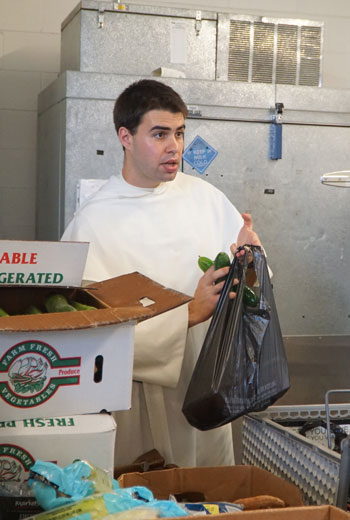 Brother Bartholomew Calvano bagged produce at the Society of St. Vincent de Paul's Food Pantry July 13. Brother Calvano and Brother Frassati Davis are spending their summer living at St. Louis Bertrand Church and working at St. Vincent de Paul.