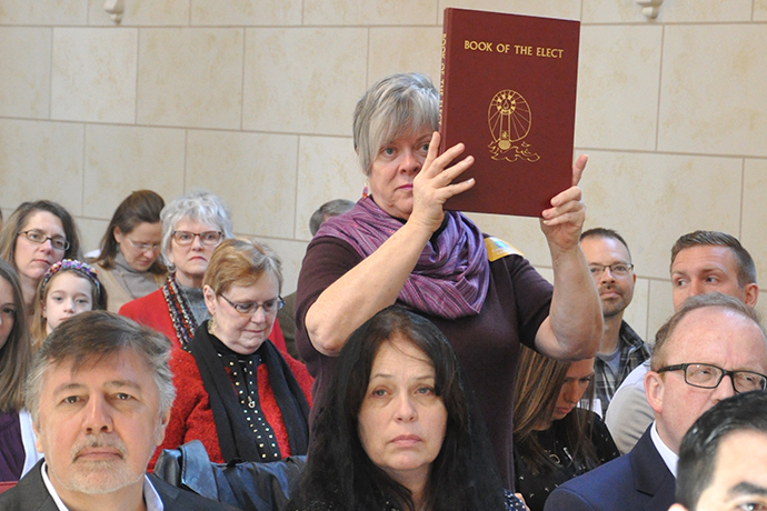 Theresa Secord, pastoral associate at St. Agnes Church in the Highlands, held the Book of the Elect during the Rite of Election ceremony in March at the Cathedral of the Assumption. Pastoral associates and other lay ecclesial ministers will benefit from a Lilly Endowment grant.