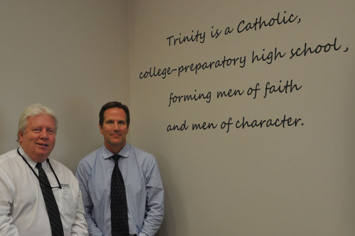 "Trinity High School President Dr. Robert J. Mullen, left, and Principal Dan Zoeller stand next to the words of the school's mission statement last week. The pair said the words ""forming men of faith and men of character"" served as a guidepost when they instituted a school-wide drug-testing policy two years ago. (Record Photo by Jessica Able)"
