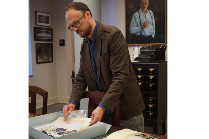 Mark Meade, assistant director of the Merton Center removed from its casing an original illustration by Ade Bethune entitled 'St. Dorothy: Martyr,' one of the hundreds of items that are now part of a digital collection accessible through a kiosk in the center. (Record Photo by Ruby Thomas)