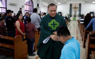 Msgr. James Benavente blesses a boy after Mass at Santa Barbara Church on the island of Guam Aug. 13. (CNS photo/Erik De Castro, Reuters) See GUAM-NORTH-KOREA-PRAYERS Aug. 14, 2017.