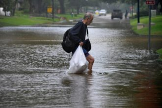 A man carries his belongings through flood waters in Houston, Texas, Aug. 28. (CNS photo/Nick Oxford, Reuters)