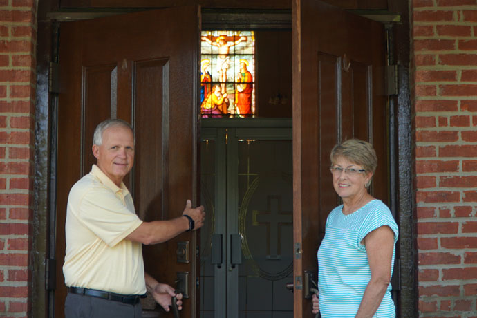 Deacon Greg Beavin and his wife Shirley stand at the entrance of St. Theresa Church in Rhodelia, Ky., Aug. 3. St. Theresa is the oldest church in Meade County and it's one of the parishes where Deacon Beavin was assigned after ordination. The deacon and his wife grew up at the parish. (Record Photo by Ruby Thomas)