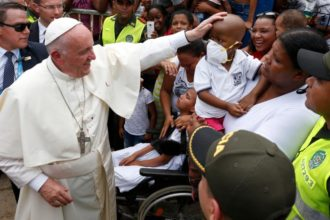 Pope Francis greets a sick child near the Talitha Qum homeless shelter in Cartagena, Colombia, Sept. 10. The pope cut his head in the popemobile when it braked suddenly. (CNS photo/Paul Haring)