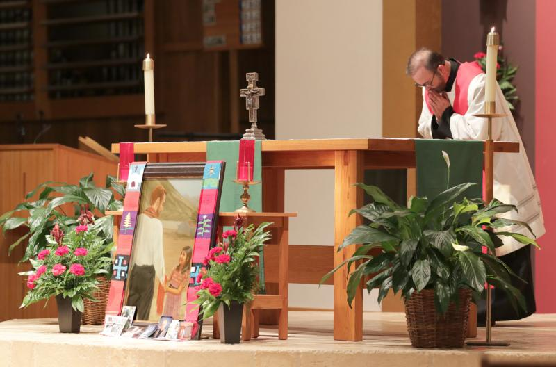 Father Joe Townsend, pastor of St. Benedict Parish in Broken Arrow, Okla., bows before the altar and an image of Father Stanley Rother during a Sept. 22 vespers and vigil. Father Rother, a priest of the Oklahoma City Archdiocese who was murdered in 1981 in the Guatemalan village where he ministered, was beautified the next day in Oklahoma City. (CNS photo/Dave Crenshaw, Eastern Oklahoma Catholic)