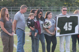 Andy Rodman, the brother of police officer Nicholas Rodman, held a framed number 45 jersey during a football game on Holy Cross High School's campus Sept. 8. A similar one will hang in the school's building. (Photo Special to The Record by Holy Cross High School)