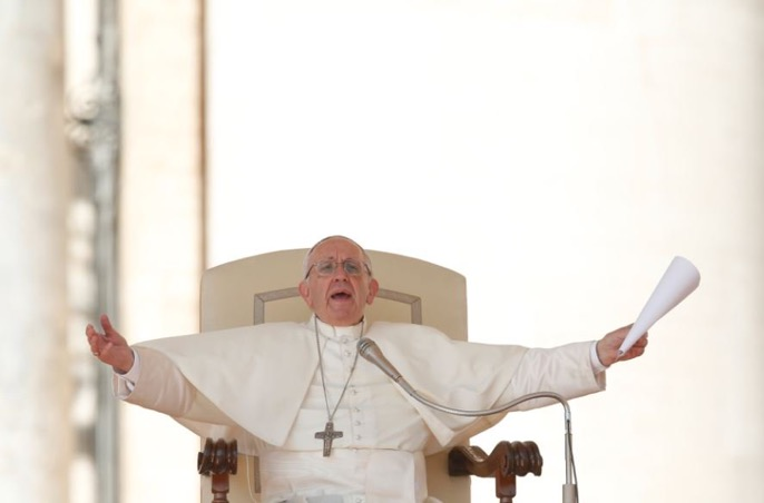 """Pope Francis makes a gesture of an embrace in support of immigrants during his general audience in St. Peter's Square at the Vatican Sept. 27. The pope made the gesture as he launched the """"Share the Journey"""" campaign in support of immigrants. The campaign is an initiative of Caritas Internationalis. (CNS photo/Paul Haring)"""
