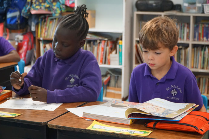 Ened Otier, left, and Dylan Clements, third-graders at St. Nicholas Academy, read from their books during class Sept. 11. Forty-three percent of St. Nicholas' 197 families receive tuition assistance. The regional school on New Cut Road has a total enrollment of 334 in prekindergarten through eighth-grade. The Catholic Education Foundation, with the support the Archdiocese of Louisville and its parishes, provided $6.5 million in tuition assistance to 3,000 students this school year. (Record Photo by Jessica Able)