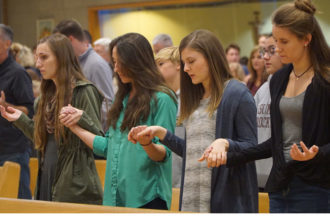 Young adults, from left, Emily Schmitt, Kelly Schmitt, Ashley Brown and Amanda Tiedtke recited the Lord's Prayer. The young women were among more than 220 who attended the annual Young Adult Mass celebrated this year at St. Albert the Great Church, 1395 Girard Drive, Oct. 15. (Record Photo by Ruby Thomas)