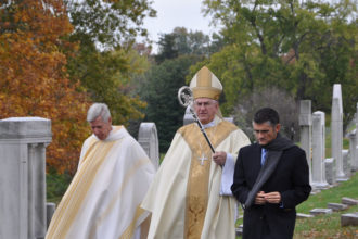 Father Gerry Bell, above left, Archbishop Joseph E. Kurtz, center, and Javier Fajardo, executive director of Catholic Cemeteries walked near headstones at Calvary Cemetery, 1600 Newburg Road, Nov. 2. Archbishop Kurtz celebrated a Mass commemorating the feast of All Souls' Day under a tent near the priests' section at Calvary. Averie Richardson, left, a seventh-grader at St. James School in Elizabethtown, Ky., dressed as Blessed Chiara Badano Nov. 1 for her school's observance of All Saints' Day.  Photos, at left and below, Special to The Record