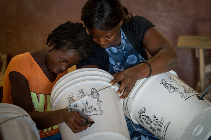 Haitian women learned about Water With Blessings' filter kits, which include a five gallon bucket, Nov. 5. The Louisville-based Water With Blessings distributes water filters to mothers in areas where clean water is hard to find. The organization launched a campaign this month to eradicate cholera in Haiti by distributing water filters to women around the nation. (Photo Special to The Record by Bryan Woolston)