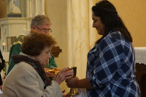 Dora Lozano presented the chalice to a parishioner during Mass at St. Dominic Church Oct. 29. (Record Photo by Ruby Thomas)