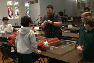 Charlie Shunnarah, the chef at St. Vincent de Paul's Open Hand Kitchen, spoke to Holy Trinity seventh-graders who helped him prepare green beans for lunch at the kitchen Oct. 31. (Photo Special to The Record)