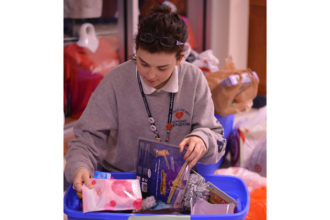 Jessica Julian, a senior at Sacred Heart Academy, packed a container destined for needy families in West Virginia. (Photo Special to The Record)